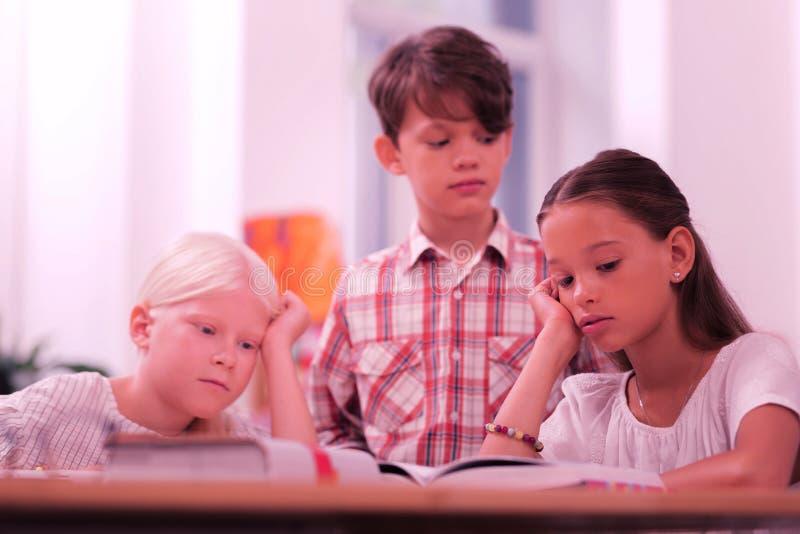 Kinderen in een klaslokaal die het boek proberen te lezen royalty-vrije stock foto