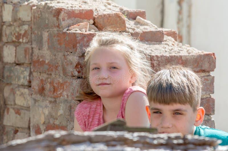 Kinderen in een verlaten en vernietigd gebouw in de streek van militaire en militaire conflicten Het concept sociale problemen va royalty-vrije stock foto's