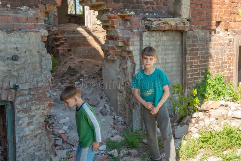 Kinderen in een verlaten en vernietigd gebouw in de streek van militaire en militaire conflicten Het concept sociale problemen va royalty-vrije stock foto