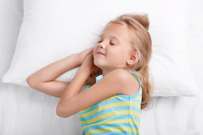 Kinderen en bedtijdconcept De mooie meisjesdutjes in bed, heeft prettige fantastische dromen, houdt ogen gesloten, draagt gestree stock afbeeldingen