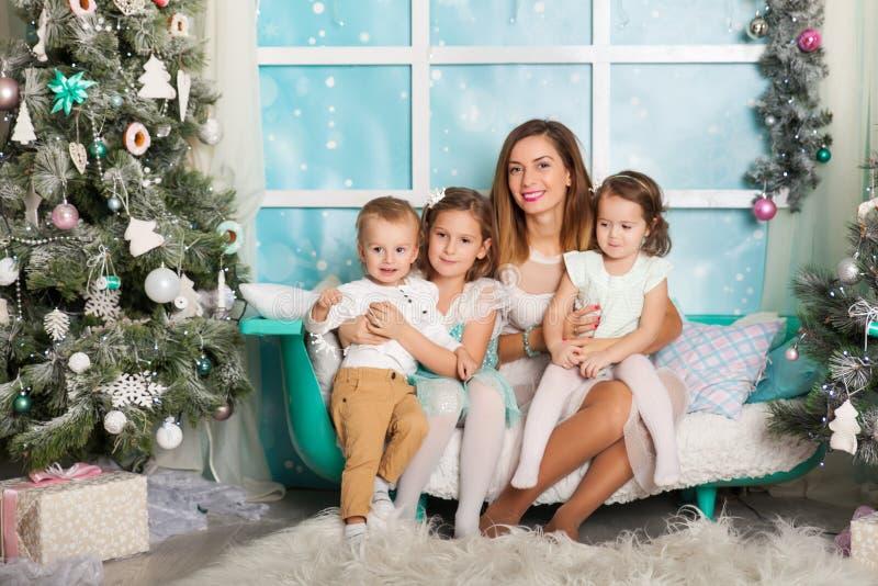 Kinderen en een jonge moeder in Kerstmisdecoratie royalty-vrije stock afbeelding