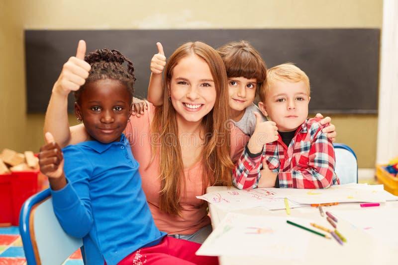 Kinderen en leraar als vrienden in kleuterschool stock foto