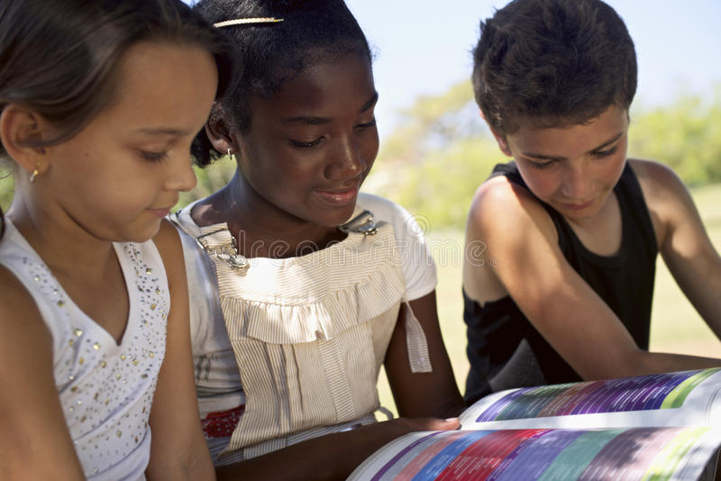 Kinderen en onderwijs, jonge geitjes en meisjes die boek in park lezen royalty-vrije stock foto
