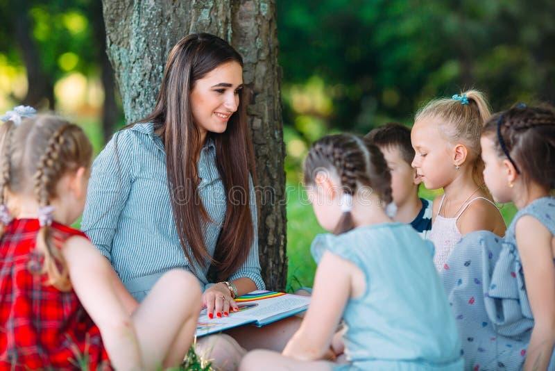 Kinderen en onderwijs, jonge vrouw op het werk als boek van de opvoederlezing aan jongens en meisjes in park royalty-vrije stock afbeelding
