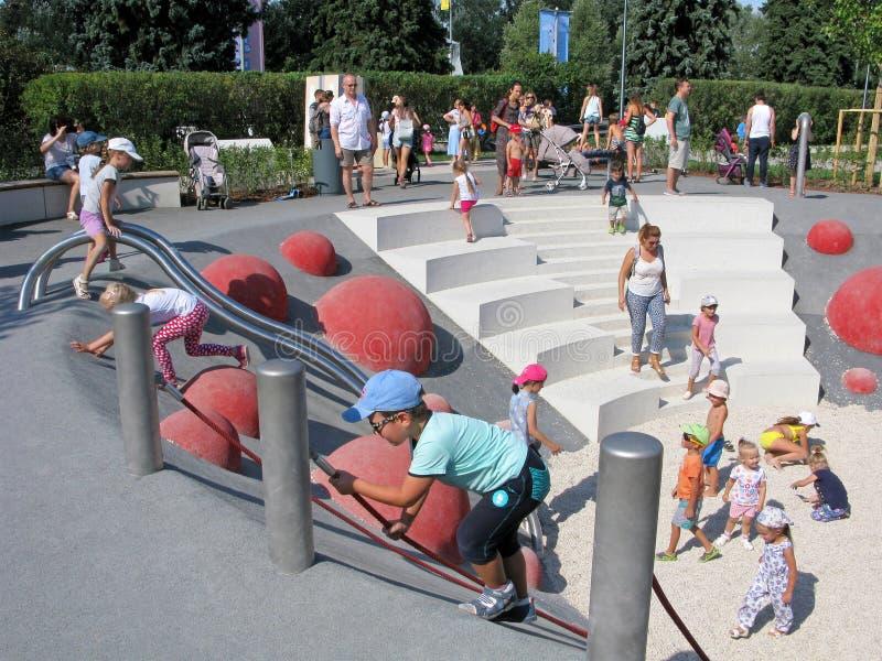 Kinderen en ouders, sportenspeelplaats, actieve rust in het park stock afbeelding