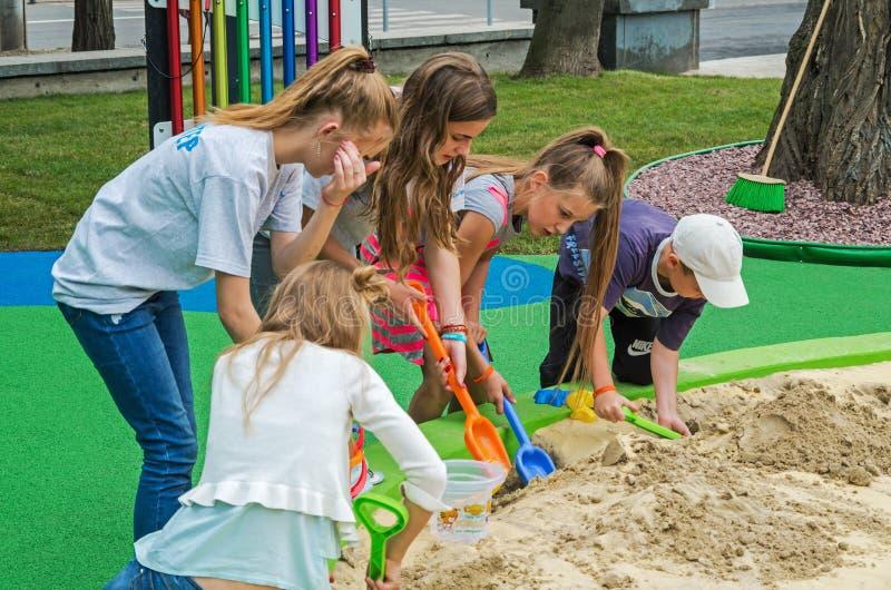 Kinderen en vrijwilligersspel in zandbak stock afbeeldingen