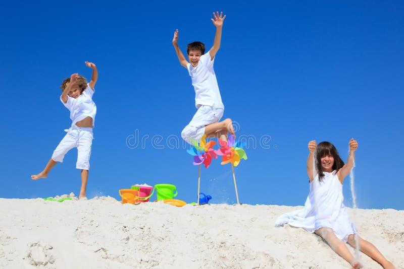 Kinderen en vuurraderen op zand royalty-vrije stock foto