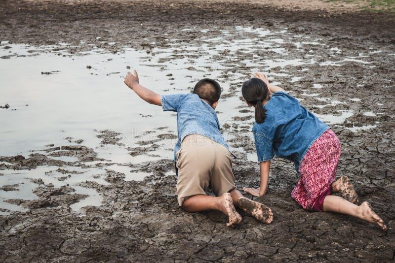 Kinderen en water op dorre grond in heet stock fotografie