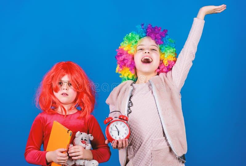 Kinderen ernstig bij hun spel Leuke kleine kinderen die kleurrijk pruikenhaar dragen Adorbale kleine kinderen met wekker stock afbeelding