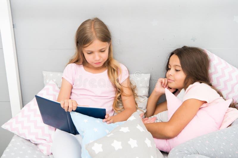Kinderen gelezen boek in bed De verhalen zouden elk jong geitje moeten lezen Familietraditie Meisjes beste vrienden voordien gele royalty-vrije stock foto's