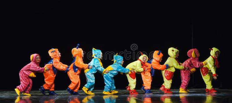 Kinderen in grappige gekleurde overallvreemdelingen die op stadium dansen stock afbeeldingen