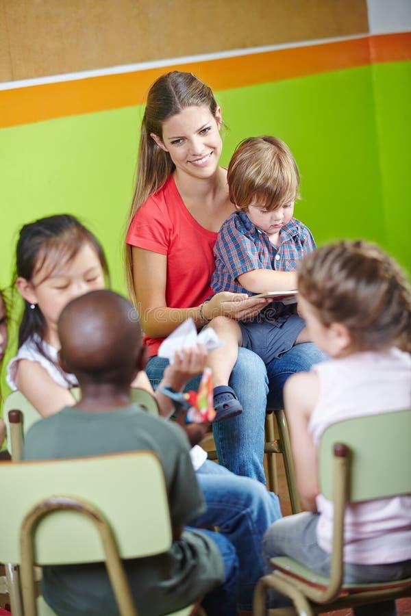 Kinderen in kleuterschoolzitting stock afbeeldingen