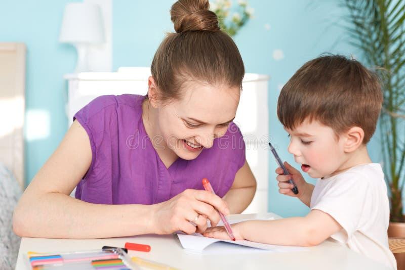 Kinderen, kunst en onderwijsconcept De glimlachende mooie jonge moeder trekt palmdruk van haar zoon op papier, samen betrokken bi stock afbeelding