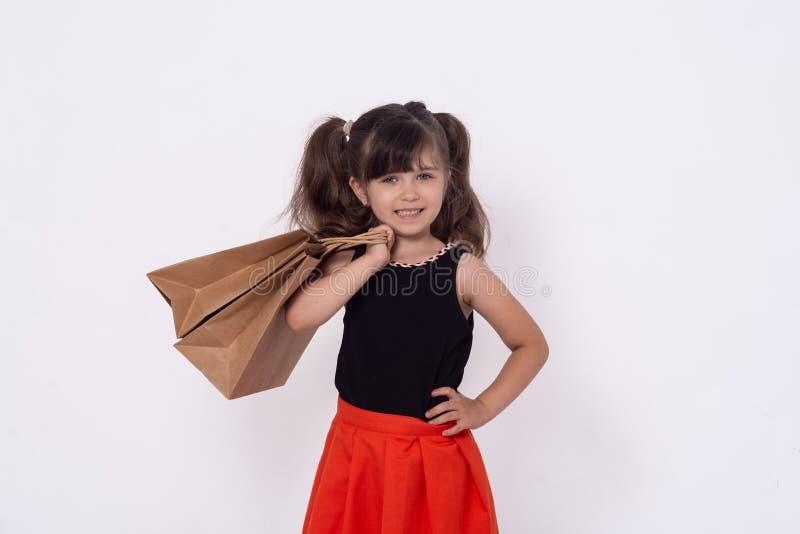 Kinderen met aankopen die op witte achtergrond worden geïsoleerd Jong geitje met het winkelen zakken stock fotografie