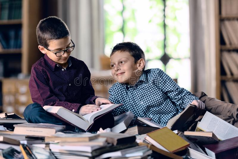 Kinderen met boeken in de bibliotheek royalty-vrije stock afbeeldingen