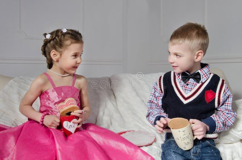 Kinderen met Cakes en Koppen stock afbeeldingen