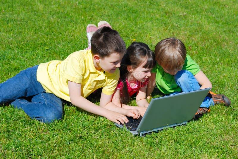Kinderen met computer openlucht stock fotografie