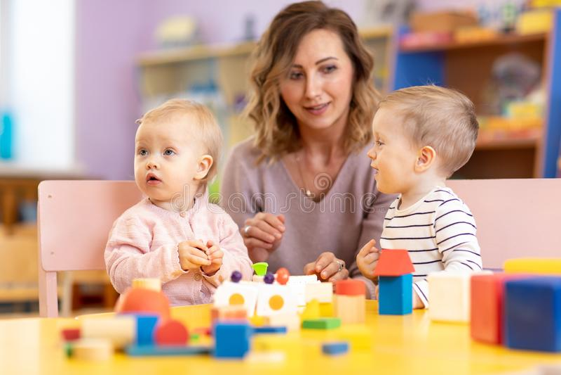 Kinderen met leraar die onderwijsspeelgoed spelen, en kleurrijke stukken stapelen schikken Lerend door ervaringsconcept, bruto royalty-vrije stock fotografie