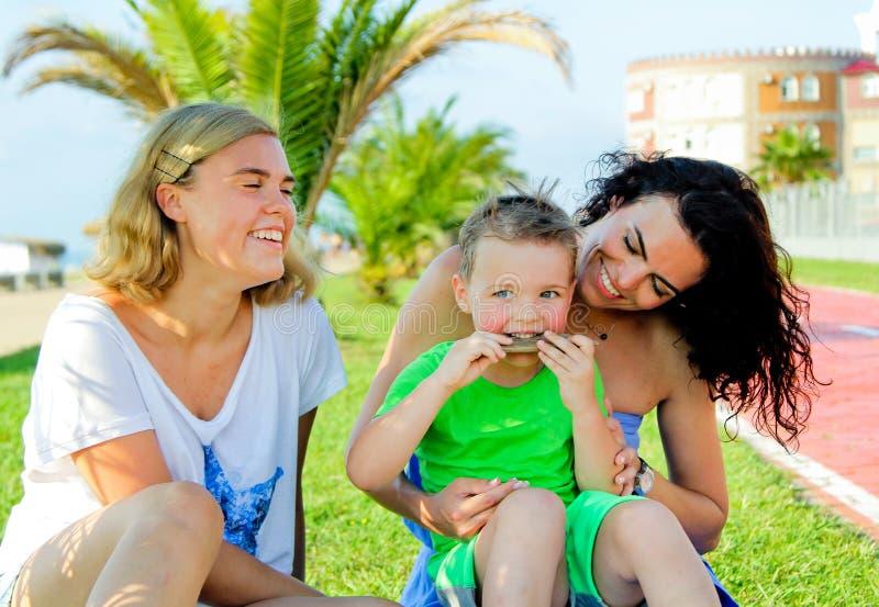 Kinderen met mamma zitting en het lachen Jongen die een stok kauwen royalty-vrije stock afbeeldingen