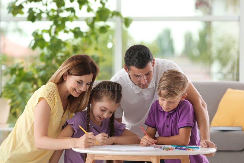 Kinderen met ouders die bij lijst binnen trekken stock foto