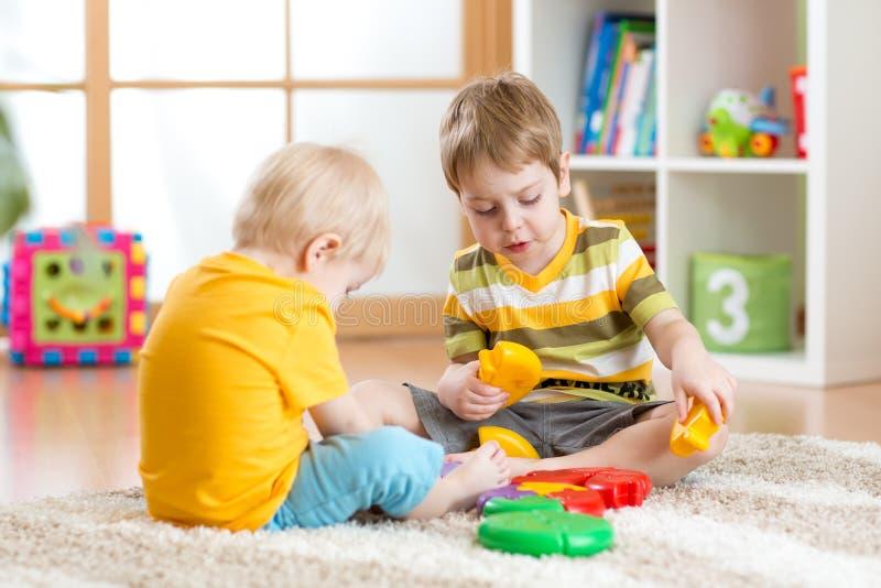 Kinderen met speelgoed in speelkamer stock fotografie