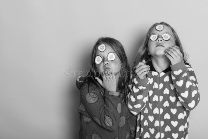 Kinderen met trotse gezichten, komkommers op ogen en los haar De meisjes in kleurrijke polka gestippelde pyjama's verzenden kusse royalty-vrije stock afbeeldingen