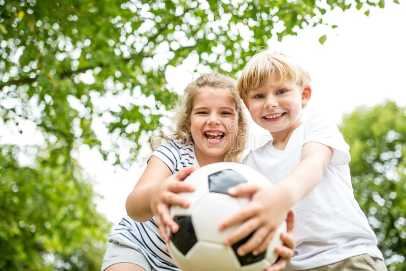 Kinderen met voetbal stock afbeelding