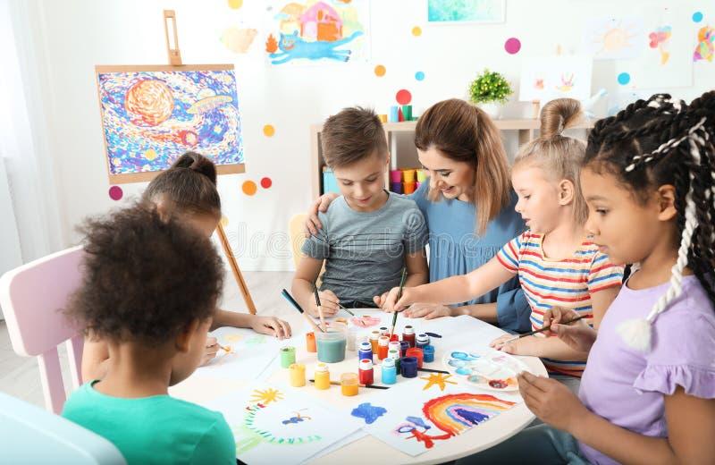 Kinderen met vrouwelijke leraar bij het schilderen les royalty-vrije stock foto's