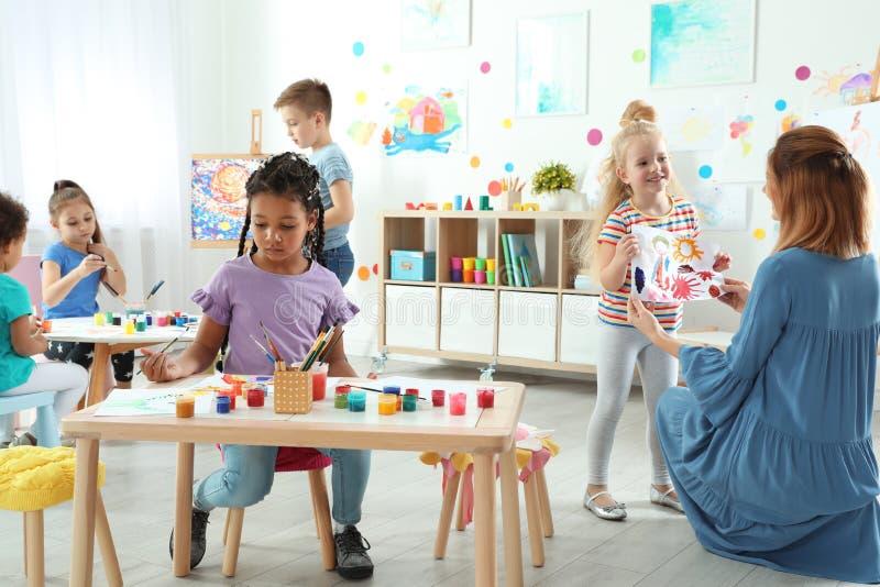 Kinderen met vrouwelijke leraar bij het schilderen les stock foto's
