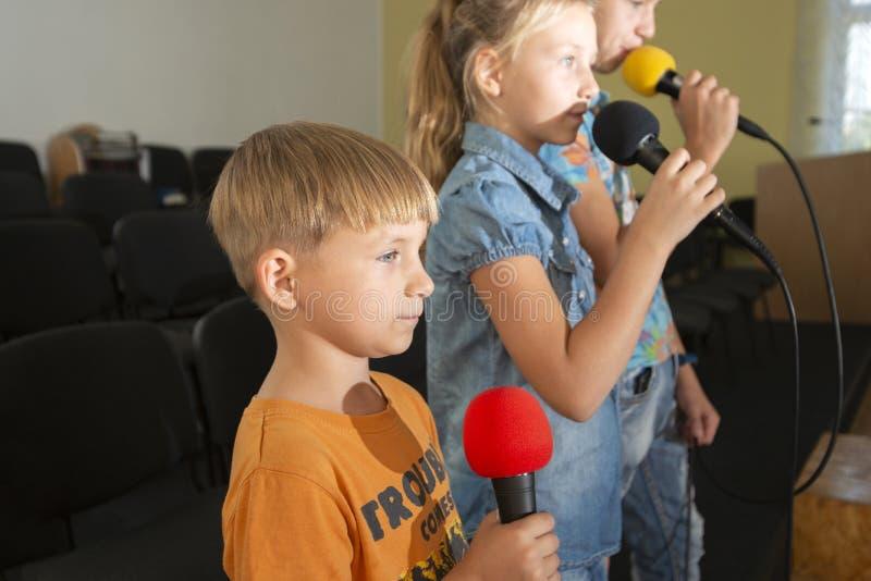 Kinderen nemen deel met een microfoon, recite gedichten, recitatie, zingen van liedjes stock afbeeldingen
