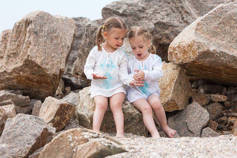Kinderen op het overzeese strand Tweelingen die tegen stenen en zeewater zitten stock fotografie