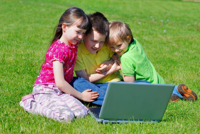 Kinderen in openlucht met laptop stock fotografie