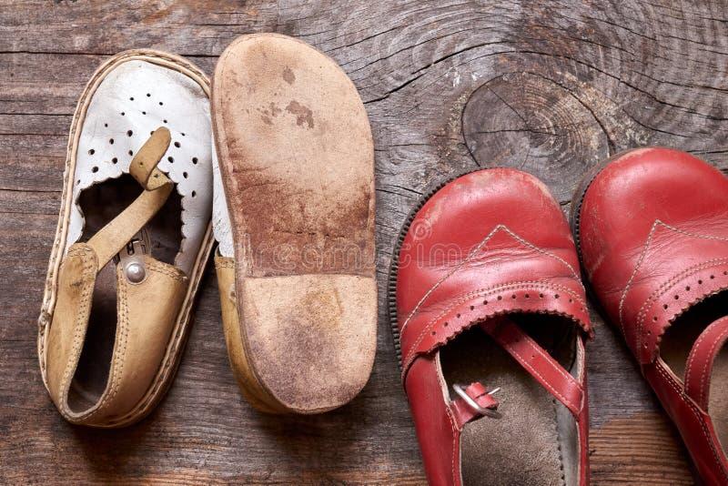 Kinderen ouderwetse schoenen op uitstekende houten close-up als achtergrond Herinnering van kinderjaren stock foto's