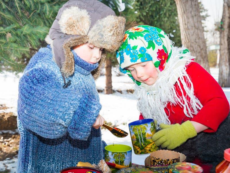 Kinderen in Russische pavloposadskiesjaal op hoofd het drinken thee op achtergrond van samovar stock foto's