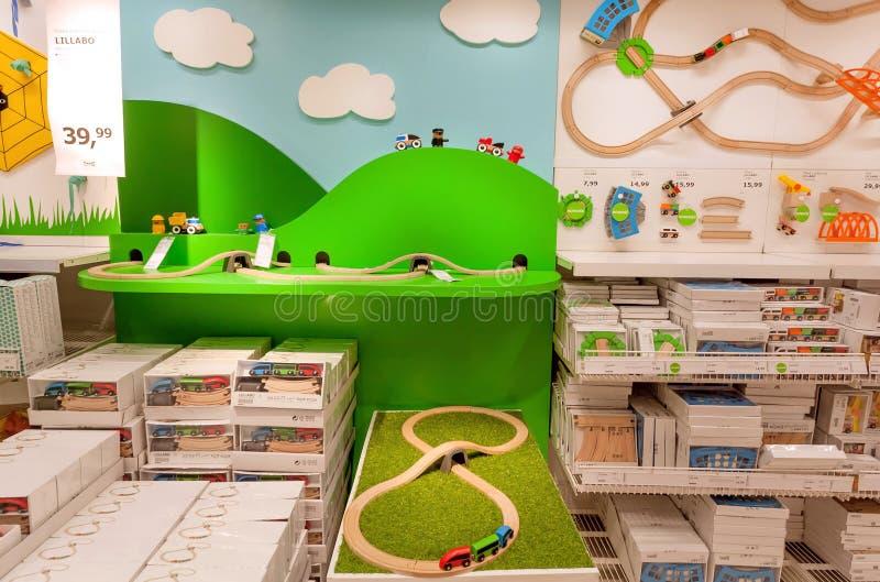 Kinderen` s afdeling met speelgoed en ontwerpproducten voor jonge geitjes in grote IKEA-opslag met meubilair, decor stock afbeeldingen