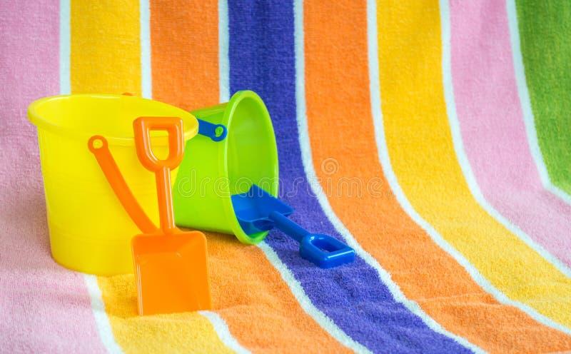 2 kinderen` s emmers en schoppen op een strandhanddoek royalty-vrije stock fotografie