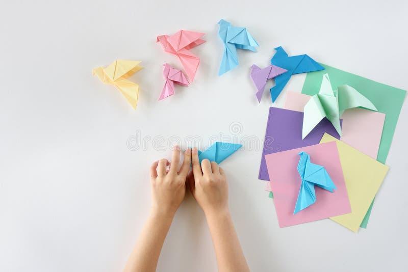 Kinderen ` s hands do origami van gekleurd document op witte achtergrond Les van origami royalty-vrije stock foto's