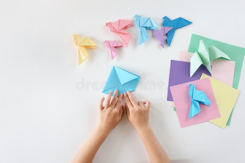 Kinderen ` s hands do origami van gekleurd document op witte achtergrond Les van origami stock afbeelding