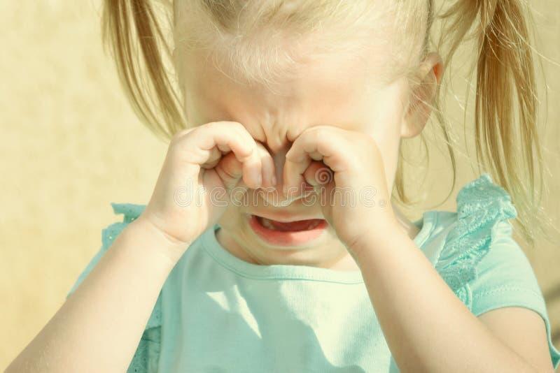 Kinderen` s hysterie Een klein meisje met blond haar schreeuwt en wrijft haar ogen met haar handen royalty-vrije stock afbeeldingen