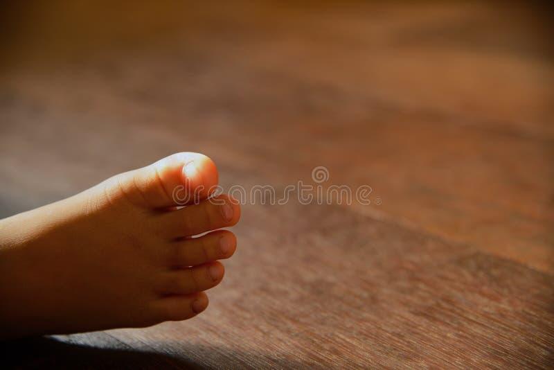 Kinderen` s naakte voeten op houten vloer stock fotografie