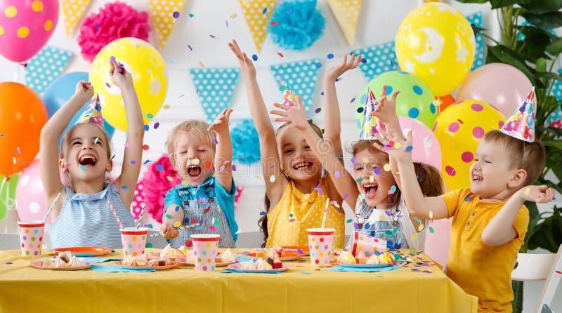 Kinderen` s verjaardag gelukkige jonge geitjes met cake stock afbeeldingen