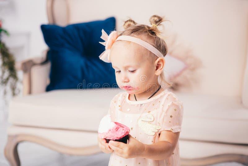 Kinderen` s verjaardag het grappige twee-jaar-oude Kaukasische meisje in roze kleding die zich aan slaapkamer van huis de achterg stock afbeelding