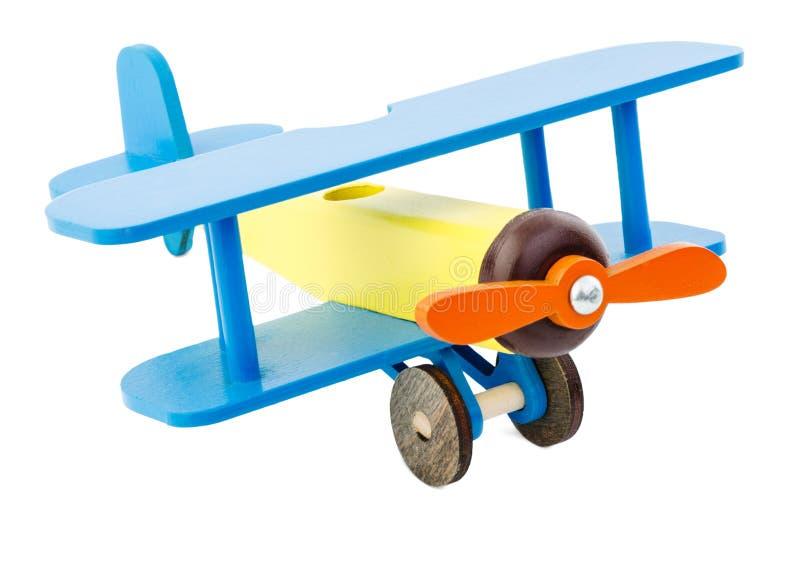Kinderen` s vliegtuig van gele blauwe die kleur van hout wordt gemaakt op witte achtergrond wordt geïsoleerd stock afbeelding