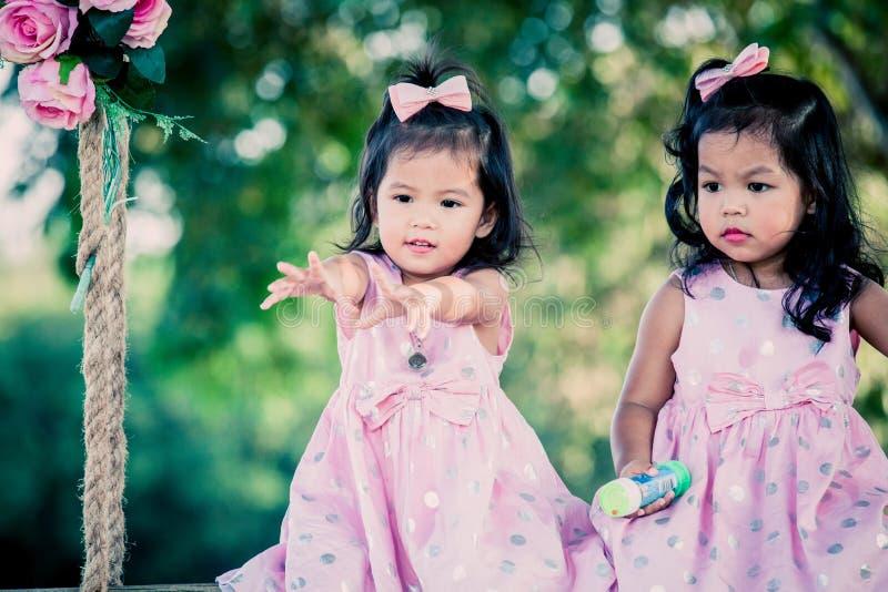 Kinderen twee leuke meisjes die op schommeling zitten stock afbeeldingen