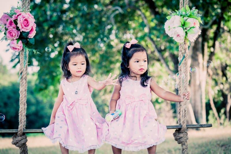 Kinderen twee leuke meisjes die op schommeling zitten royalty-vrije stock foto's