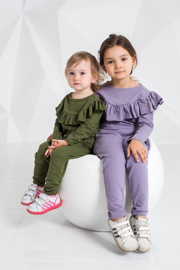 Kinderen, twee zusters 1 5 en 5 jaar oud in de identieke kostuums van verschillende kleuren, meisjes op een wit royalty-vrije stock foto's