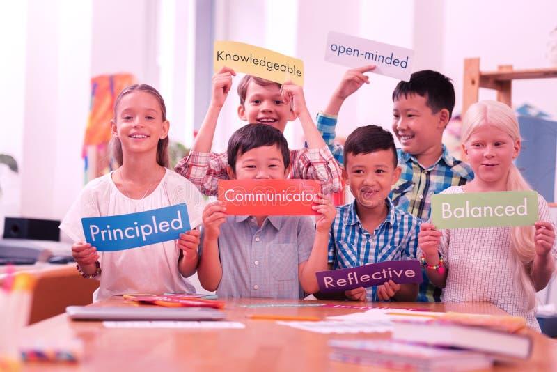 Kinderen van verschillende rassen die kleurrijke bijvoeglijke naamwoorden houden royalty-vrije stock afbeelding