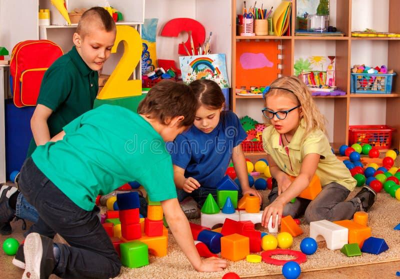 Kinderenbouwstenen in kleuterschool Groepsjonge geitjes die stuk speelgoed vloer spelen royalty-vrije stock fotografie