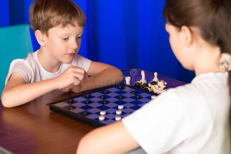 Kinderenjongen en meisje die een raadsspel genoemd spelen Controleurs royalty-vrije stock foto's
