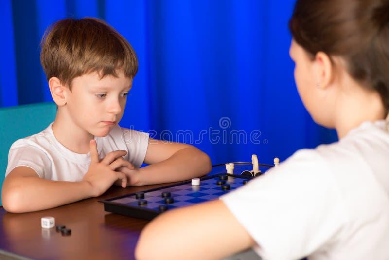 Kinderenjongen en meisje die een raadsspel genoemd spelen Controleurs royalty-vrije stock fotografie